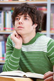 Reading. Portrait of smart lad thinking while reading book in library Royalty Free Stock Images