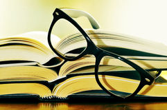 Reading. A pile of books and glasses symbolizing the concept of reading habit or studing Stock Images