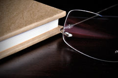 Reading. Eyeglasses next to a book on top of a wood table Stock Photos