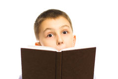 Reading. Boy holding a book with a surpised look Royalty Free Stock Photos