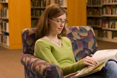 Reading. A young woman sitting in a chair at the library reading a magazine Stock Photography