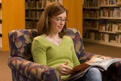 Reading. A young woman sitting in a chair at the library reading a magazine Royalty Free Stock Images