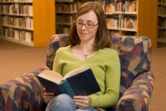 Reading. A young woman sitting in a chair at the library reading a book Royalty Free Stock Photo