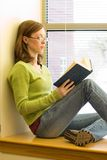 Reading. A young woman sitting on a window sill at the library reading a book Stock Images