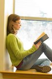Reading. A young woman sitting on a window sill at the library reading a book Royalty Free Stock Photos