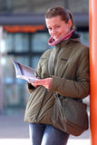 Reading. A young attractive woman standing in front of the train station and reading a tourist guide Royalty Free Stock Image