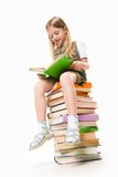 Reading. Image of schoolgirl sitting on the heap of books and reading one of them Stock Image