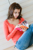 Reading. An attractive young woman reading her magazine Stock Photos