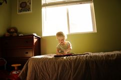 Reading. A young boy in his bedroom reading a book Stock Images