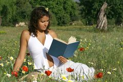 reading. Pretty Girl reading in meadow Stock Images