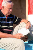 Reading. Elderly man sitting and reading a book Stock Photos