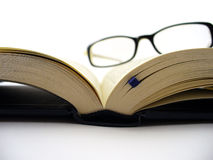 Reading. Eye Glasses on the book with focus on pages Royalty Free Stock Photos
