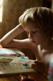 Reading ABC book. Boy reading ABC book in the house stock photography