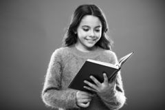 Reading activities for kids. Girl hold book read story over orange background. Child enjoy reading book. Book store
