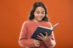 Reading activities for kids. Girl hold book read story over orange background. Child enjoy reading book. Book store. Concept. Wonderful free childrens books stock photography