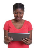 Reading african woman in red shirt with tablet Stock Images