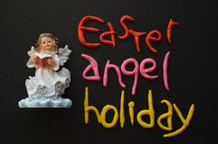 Reading Angel Figurine, Easter  Holiday Composition in White, Black, Pink, Red and Yellow Royalty Free Stock Image