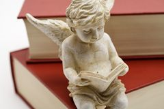 Reading angel sitting on a book. Reading angel sitting on top of a book stock photos