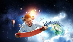 Reading as self education. Mixed media. Funny guy with book in hands levitating in air. Mixed media. Elements of this image are furnished by NASA stock images
