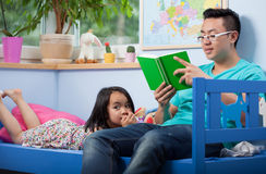 Reading asian dad and his daughter Stock Images