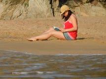 Reading on the beach Stock Photo