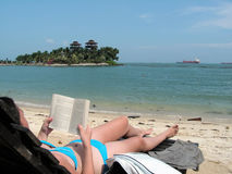 Reading at the beach. Lady suntanning and reading Royalty Free Stock Photos