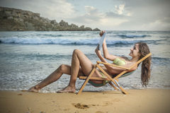 Reading at the beach. A girl is reading something at the beach Royalty Free Stock Photos