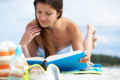 Reading on the beach Stock Photography