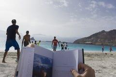 reading on the beach stock photos