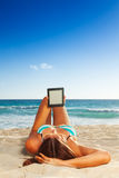Reading on beach Stock Photography