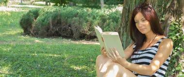 Reading. Beautiful woman reading a book Stock Photos