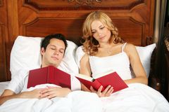 Reading in bed. A young attractive woman in bed is reading a book, while the man is sleeping Stock Images