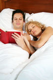 Reading in bed. A young attractive man in bed is reading a book, while the woman is sleeping Stock Photo