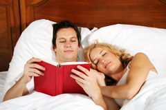 Reading in bed. A young attractive man in bed is reading a book, while the woman is sleeping Stock Images