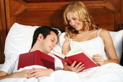 Reading in bed. A young attractive woman in bed is reading a book, while the man is sleeping Royalty Free Stock Photos