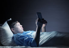 Reading in bed stock photography