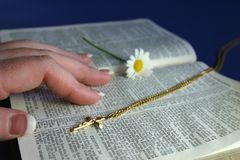 Reading Bible. Hand touching pages of open bible with gold crucifix and flower Royalty Free Stock Photo