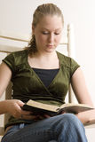 Reading the Bible. Young Caucasian woman seated in a chair reading the Bible Stock Photos