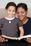 Reading The Bible. Minority woman and her daughter reading the Bible Stock Images