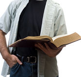 Reading The Bible. A young man reading the bible, isolated against a white background Royalty Free Stock Image