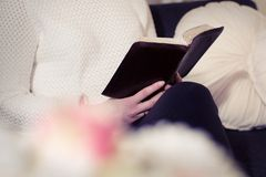 Reading the Bible alone in a sofa Royalty Free Stock Photo
