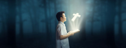 Reading the bible and faith in God. Young boy reading the bible in the dark forest. Virtual hologram cross coming out of the book. Wonderful World Royalty Free Stock Images