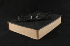 Reading The Bible. The holy bible on a black background with a pair of glasses sitting on top Royalty Free Stock Photography