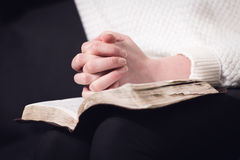 Reading bible and pray. Christian woman pray and folding hands over the holy bible Royalty Free Stock Photo