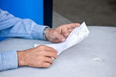 Reading a bill. A man reading a bill in his hands Stock Photo