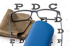 Reading black eyeglasses, brown microfiber cleaning cloth and blue protective case on white eye chart. Close-up Stock Images