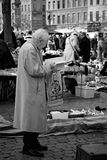 Reading. A black and white picture of an elderly man deeply concentrated reading in a book on a flea market in Brussels