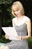 Reading blonde girl. Blonde girl in a striped dress reading at park Stock Images