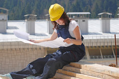 Reading blueprint. Woman in uniform reading blueprint on roof Royalty Free Stock Photo