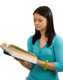 Reading a Book. Young woman reading a large book Stock Images